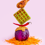A fried chicken leg balanced on top of a green waffle, balanced on top of a chili pepper, balanced on top of a red cabbage covered in peanut sauce sat on top of shredded carrot on a pink background