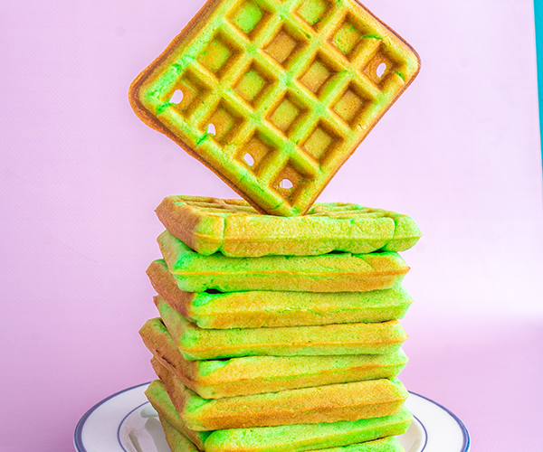 A white plate with a blue trim with a stack of green pandan waffles stacked on top, the top waffle appear to be floating on top of the stack vertically and then diagonally, there is a soft pink background with a slight edge of turquoise in the top right corner.