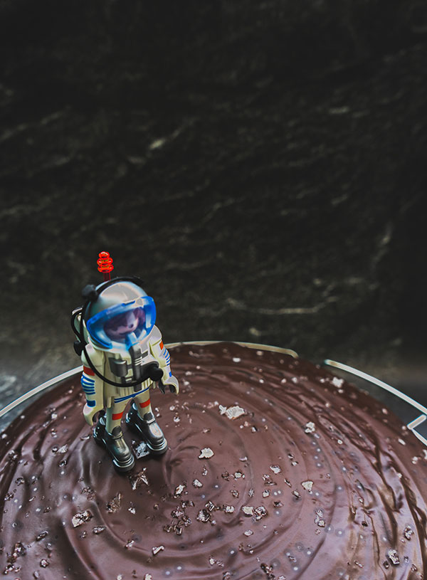 A Playmobil astronaut figure on a moon like landscape of a chocolate cake