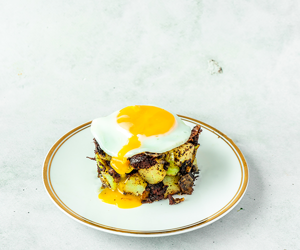 A gold trimmed white plate on top of a cement background, on the plate is a little stack of potato, Brussel sprout and black pudding hash, topped with a fried egg. The yolk of the egg is drizzling down the front of the stack.