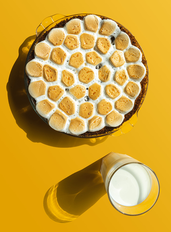 An overhead shot of a pie covered in toasted marshmallows, with the edges of a brown crust peeking out and a glass of milk at the right hand bottom corner of the image on a bright yellow background. Both the pie dish and the glass of milk leave harsh shadows on the backdrop.