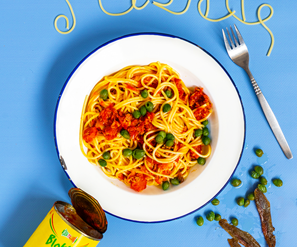An overhead shot of a white enamel plate with a blue trim on top of a blue background. The plate is filled with spaghetti, red sauce and capers. To the left bottom of the plate is an empty tomato tin, scattered at the bottom right are some capers and anchovy filets. There is a fork at the side of the plate. At the top Dorothy Porker has written PUTA in spaghetti.