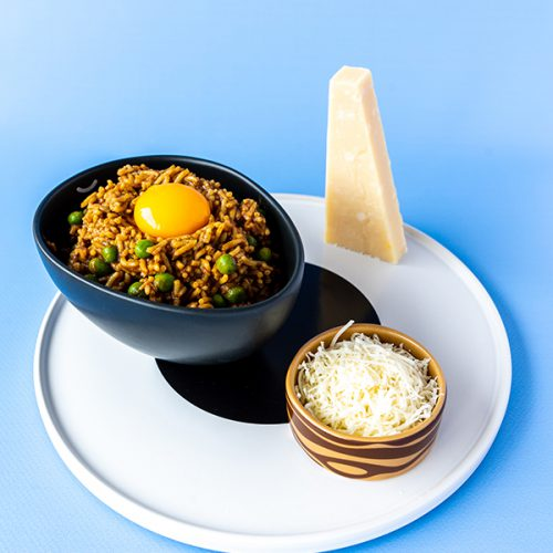 A blue background with a white plate with a black circle on top. On the plate to the right front there is a small brown and wood patterned dish with some grated Parmesan inside. To the back and left on the plate is an oval black bowl, filled with dark yellow brown rice dotted with peas, topped with a golden egg yolk. A wedge of parmesan has been set on it's backend to the right backend of the plate.