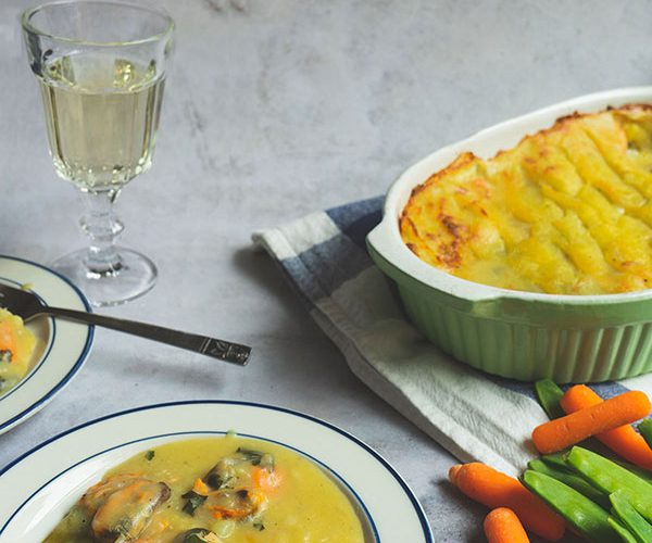 A retro 70s photography on a concrete background with a white plate with blue trim at the front with some fish pie on top. To the right of the plate are some carrots and sugar snaps. In the background is a glass of wine and to the right side there is an oven dish of fish pie set atop a white and blue dish towel.