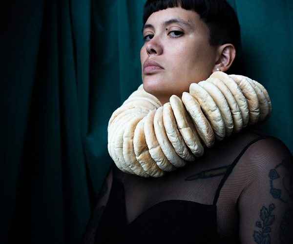 A portrait of Dorothy Porker in the old Dutch master style with a collar made of pita breads in front of a turquoise curtain