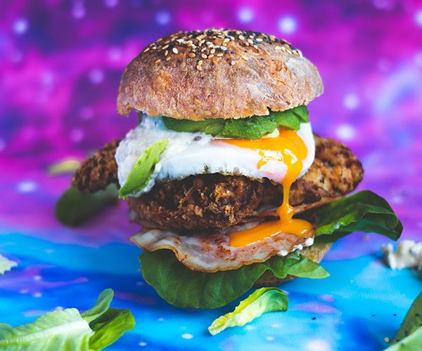 A Caesar fried chicken burger with a runny egg yolk on a space backdrop surrounded by leaves of lettuce