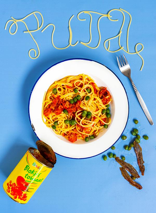 A white plate of spaghetti with red sauce and capers, surrounded by an empty tin of tomatoes, some scattered capers and anchovy filets, a fork and the word PUTA spelled in spaghetti above, on a blue background