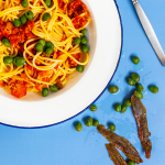 A white plate of spaghetti with red sauce and capers, surrounded by some scattered capers and anchovy filets and a fork on a blue background