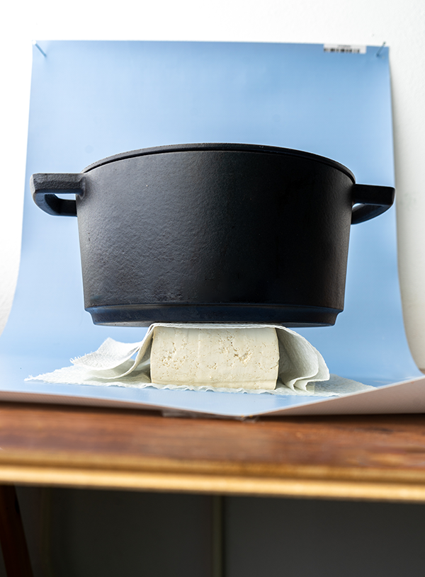 A block of tofu, pressed between two sheets of kitchen towel with a heavy cast iron pan.