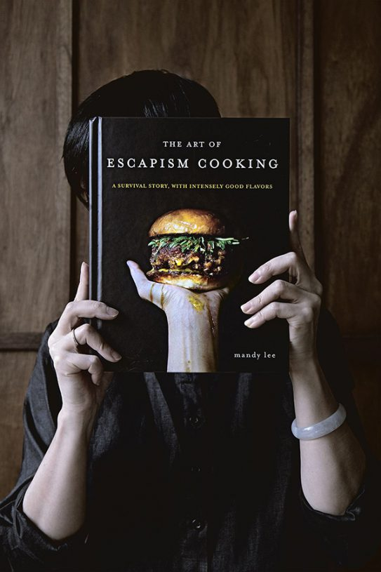 A picture of Mandy from Lady and Pups hiding behind a copy of her book The Art of Escapism Cooking