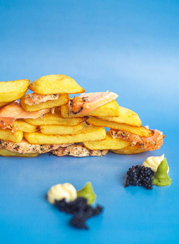 A wall of fries interspersed with flakes of smoked salmon and surrounded by tufts of mayo, wasabi and caviar