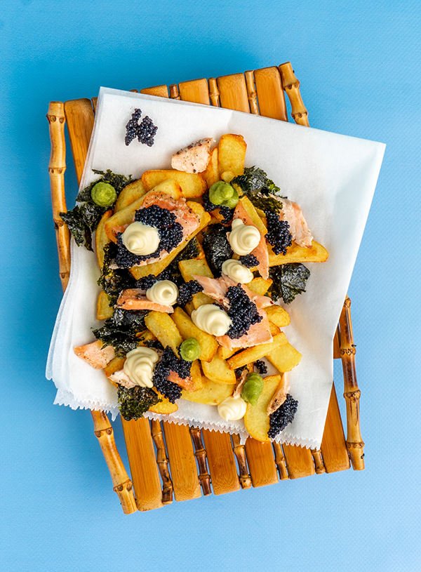 A bamboo plate filled with fries, flakes of smoked salmon, tufts of wasabi and mayo and dollops of caviar