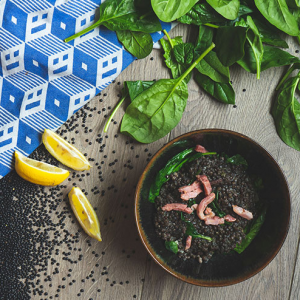 A bowl of black lentil soup with bacon and spinach, surrounded by lemon wedges, raw black lentils, spinach and a blue checkered tea towel