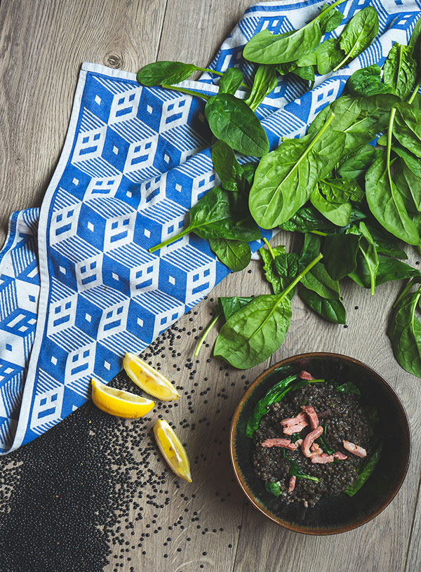 A bowl of black lentil soup with spinach and bacon bits, surrounded by raw black lentils, lemon wedges, fresh spinach and a checkered blue tea towel