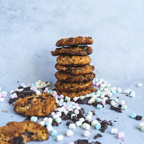 A stack of peanut butter smores cookies surrounded by chocolate chips and mini marshmallows