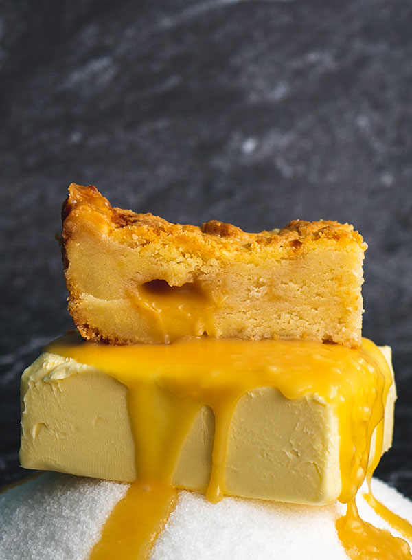 A butterbar stacked on top of caramel sauce dripping over a whole stick of butter set on a mountain of sugar