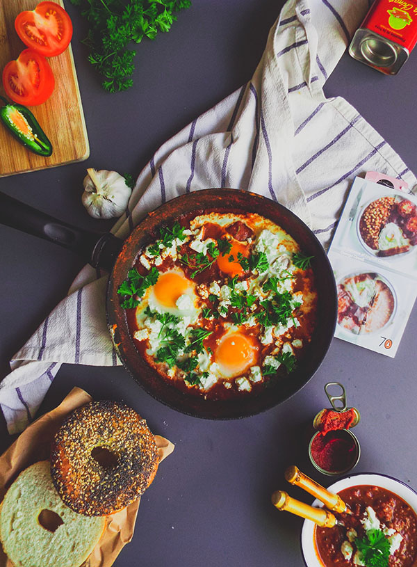 A frying pan with shakshuka, surrounded by bagels and some ingredients