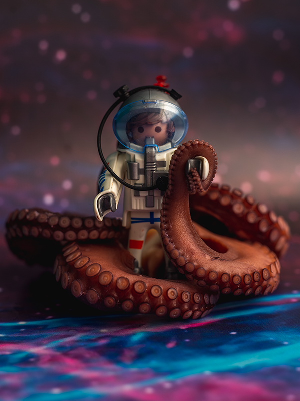 A Playmobil astronaut, surrounded by purple cooked octopus tentacles on a space backdrop