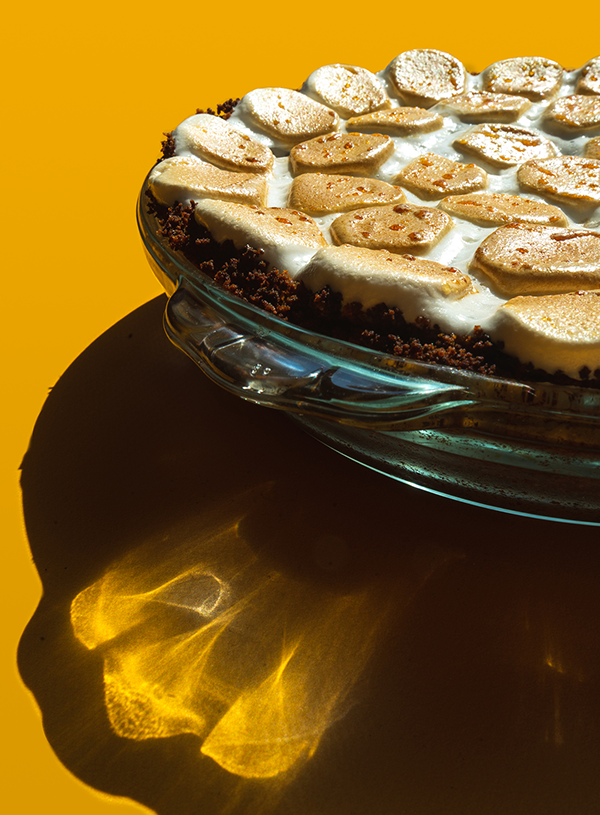 A close-up of a smores pie on a yellow background