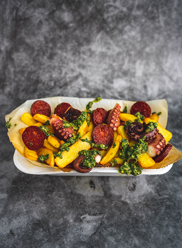 Loaded fries with octopus, chorizo and salsa verde in a Styrofoam bowl on a black concrete background