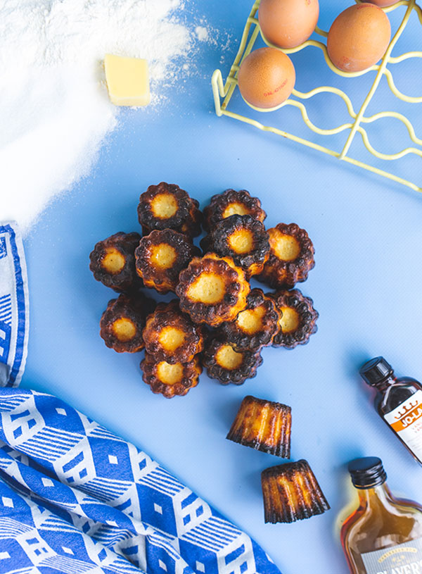 An overhead shot of a stack of canelés Bordelais surrounded by the ingredients to make them