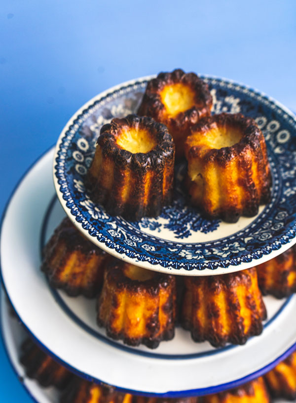 A stack of canelés Bordelais in white and blue plates