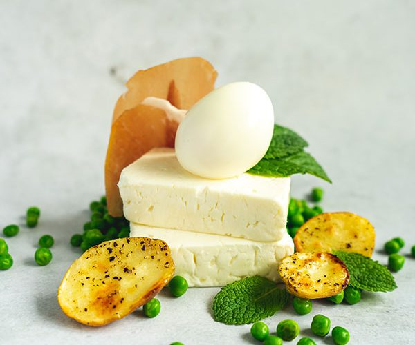Two blocks of feta with a boiled egg balancing on top, surrounding by new potatoes, peas, mint and dry-cured ham