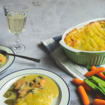 An oven dish of fish pie with a glass of white wine and two plates of fish pie