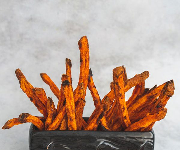 Oven baked sweet potato fries composed inside a small wooden log