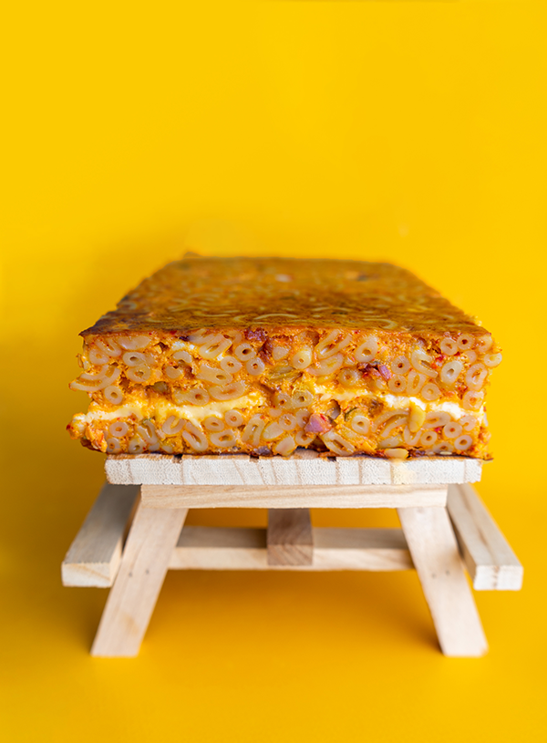 A picknick table with a slab of kimchi mac and cheese on top