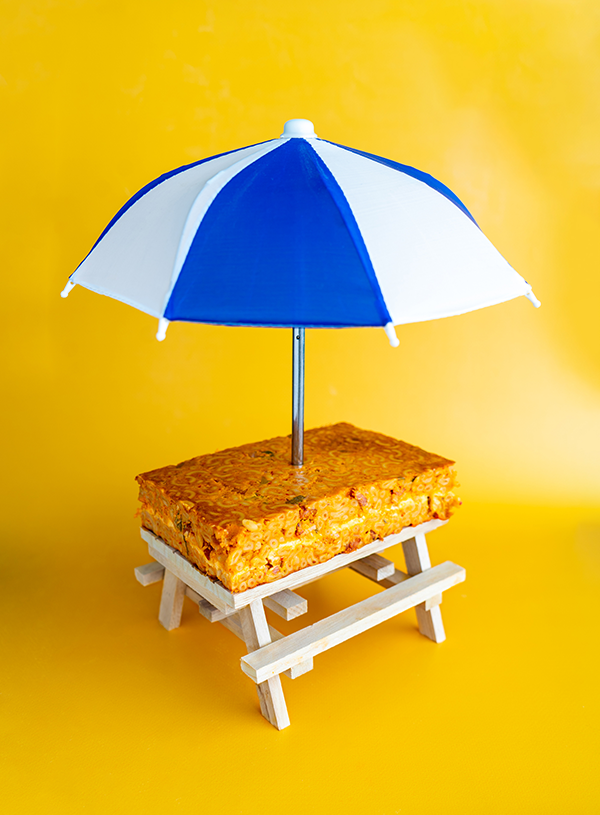 A picknick table with a slab of kimchi mac and cheese on top and a blue and white umbrella stuck into it on a yellow background