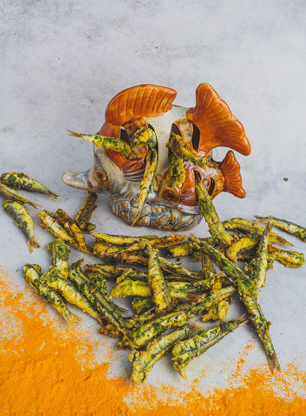 A ceramic fish surrounded by kothmiratil macchi coastal Indian coriander fried fish