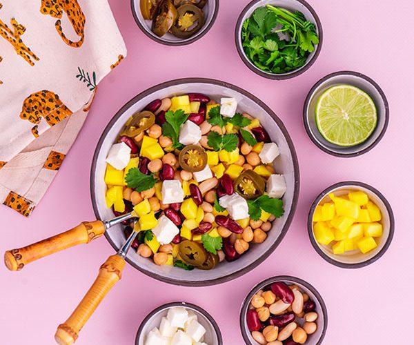 A bowl of mango, bean and feta salad surrounded by its ingredients
