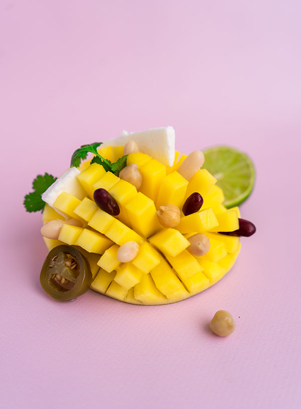 An inside out carved mango with the ingredients for mango bean salad scattered over them