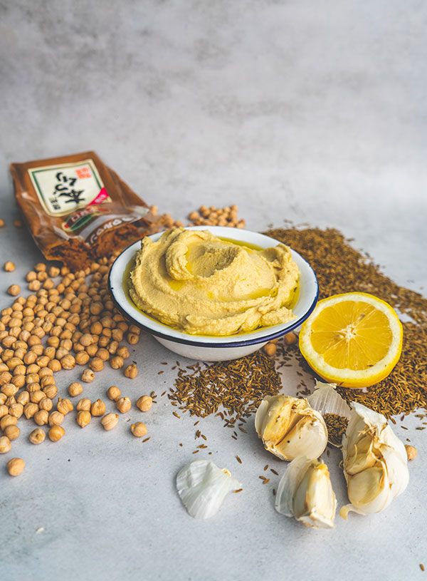 A bowl of miso amped hummus surrounded by its ingredients