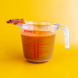 A pint of shellfish stock in a Pyrex measuring cup with the head of a prawn balancing on the rim