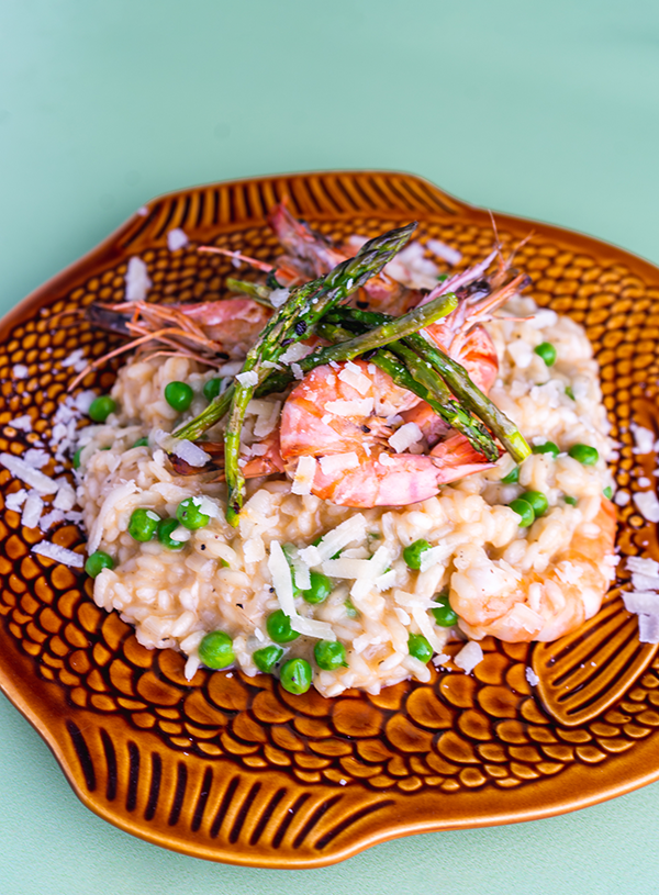 A brown fish shaped plate with a portion of seafood risotto with peas and green asparagus on top