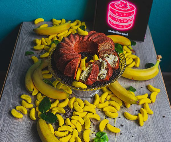 A banana curry cake surrounded by Haribo candy bananas and the book All About Cake by Christina Tosi