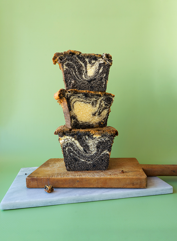Slices of black sesame swirl pound cake stacked on top of each other on marble and wooden cutting boards with a light green background