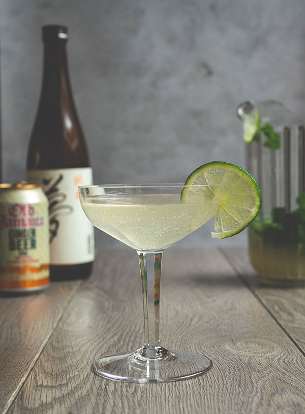 A champagne glass filled with the Japanese mule cocktail with a thin slice of lime on the rim, with a bottle of sake and a can of ginger beer in the background to the left and a jug of Japanse mule cocktail in the background to the right