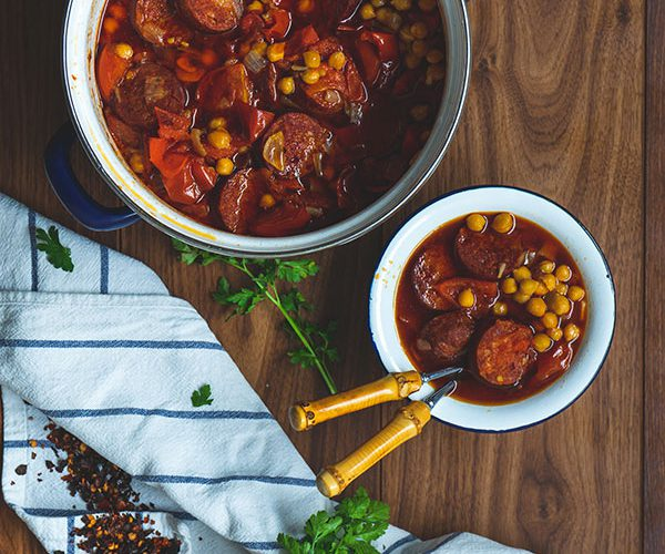 A large pot of Nigel Slater's chickpea and chorizo stew, with some of the stew to the side of it in a white enamel and blue trimmed bowl, surrounded by a white and blue striped dish towel with chipotle chili flakes, roma tomatoes and fresh flatleaf parsley draped over the top