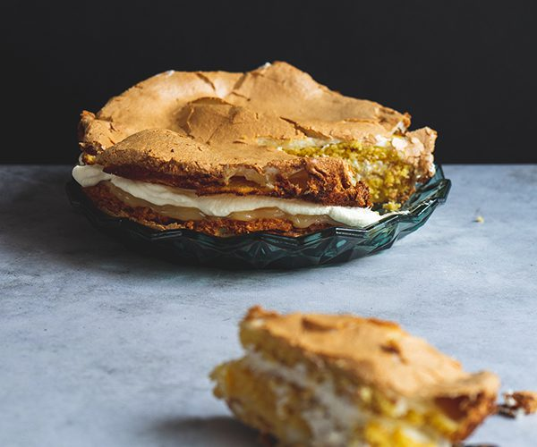 Nigella's lemon meringue cake on a plate on a concrete backdrop with a black background, with a slice of the cake cut out and out of focus in the foreground