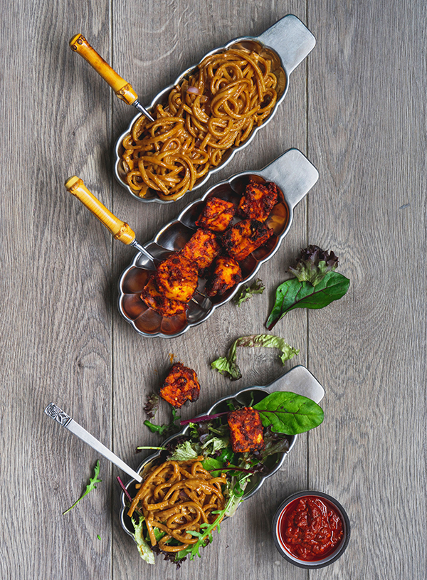 Three long metal scalloped plates with, from top to bottom, tahin noodles, harissa tofu puffs, both of those together in one plate with some mixed salad leaves and a small bowl of harissa paste