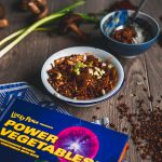 A small white enamel bowl with a blue rim, filled with vegan mushroom mapo tofu on a grey laminate background surrounded by sichuan peppercorns, spring onions, shiitake mushrooms and the book Lucky Peach presents Power Vegetables
