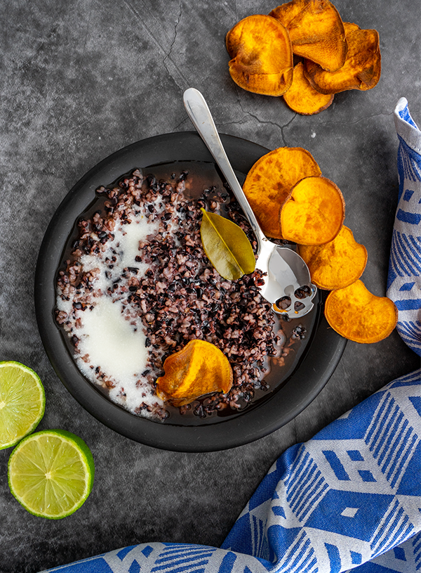A black plate with black rice pudding and white coconut milk with a skull shaped teaspoon and a lime leaf, with fried sweet potato chips and a halved lime on the side