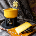 A pot of cheese fondue with a Swiss cross covered in cheese hovering above it and a block of extra spicy Appenzeller in front of it