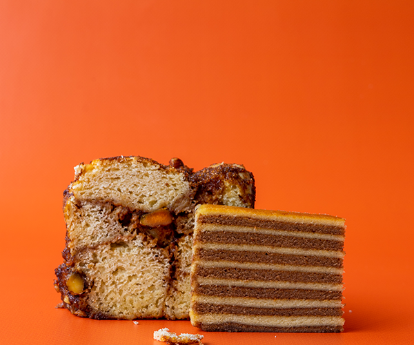 A slice of monkey bread flanked by a slice of kue lapis legit (Indonesian thousand layer cake) on a bright orange background.