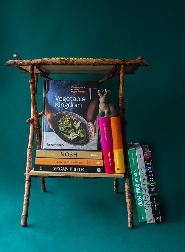 A little bamboo side table is filled with 10 vegan cookbooks, mentioned in the article. There is a little toy jackalope sitting on top of some of the books.