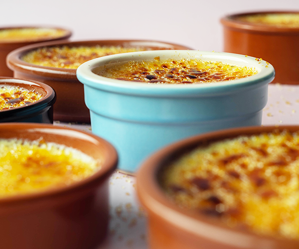 Seven bowls of crème brûlée sit together on a pink backdrop. The bowls are different heights. All the brown bowls are out of focus. One blue bowl in the center of the image is in focus.
