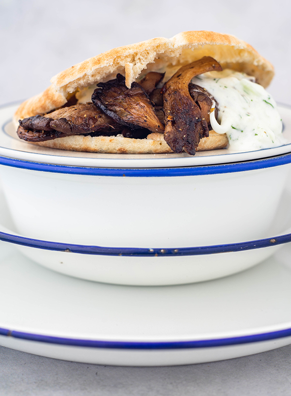 A close up of five white bowls and plates with blue trim, topped with a pita bread cut through the middle filled with roasted oyster mushrooms and tzatziki.